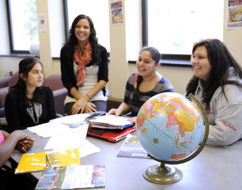 Adelphi students in classroom with a globe of the world.