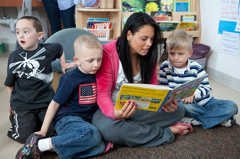teacher reads a book with three small children in classroom