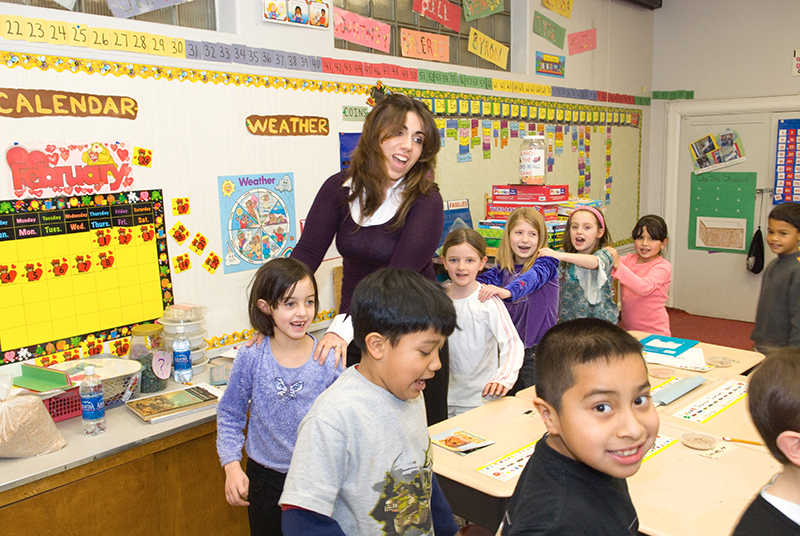 Adelphi student leading fun activity in class with grade school aged children
